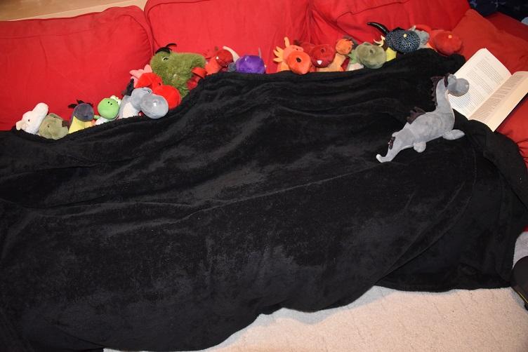 Drachen kuscheln bei der Vorlesestunde auf dem Sofa
